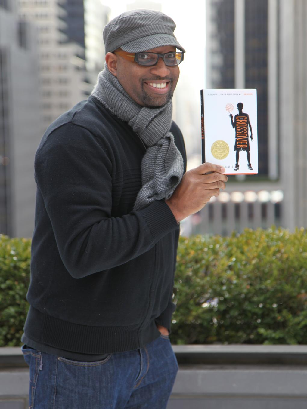 """Author Kwame Alexander holding a copy of """"The Crossover"""""""