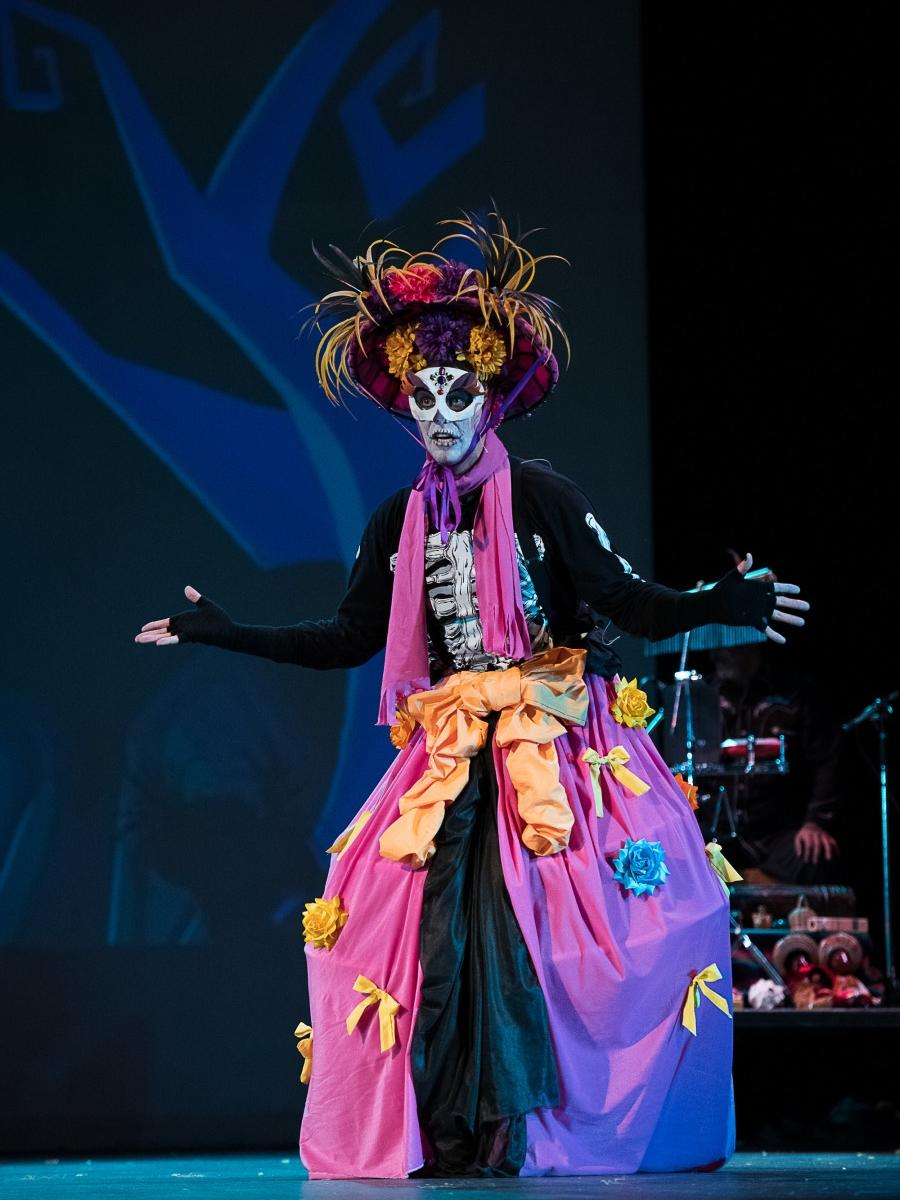 An actor wears a skull-themed costume and dress.