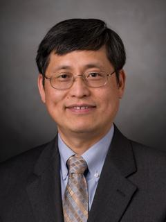 A headshot of a professor wearing glasses.