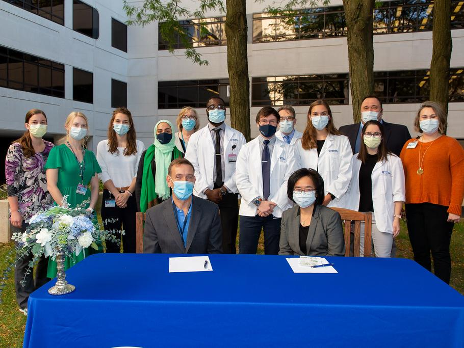 A group of medical students stand behind a table with the Dean of the College of Medicine and another woman seated at a table in front of them. Everyone is outdoors and wearing masks.