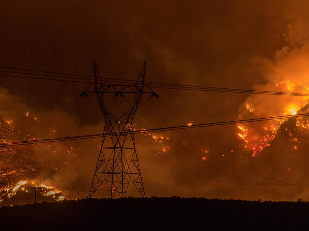 Wildfires in California burn behind transmission lines.