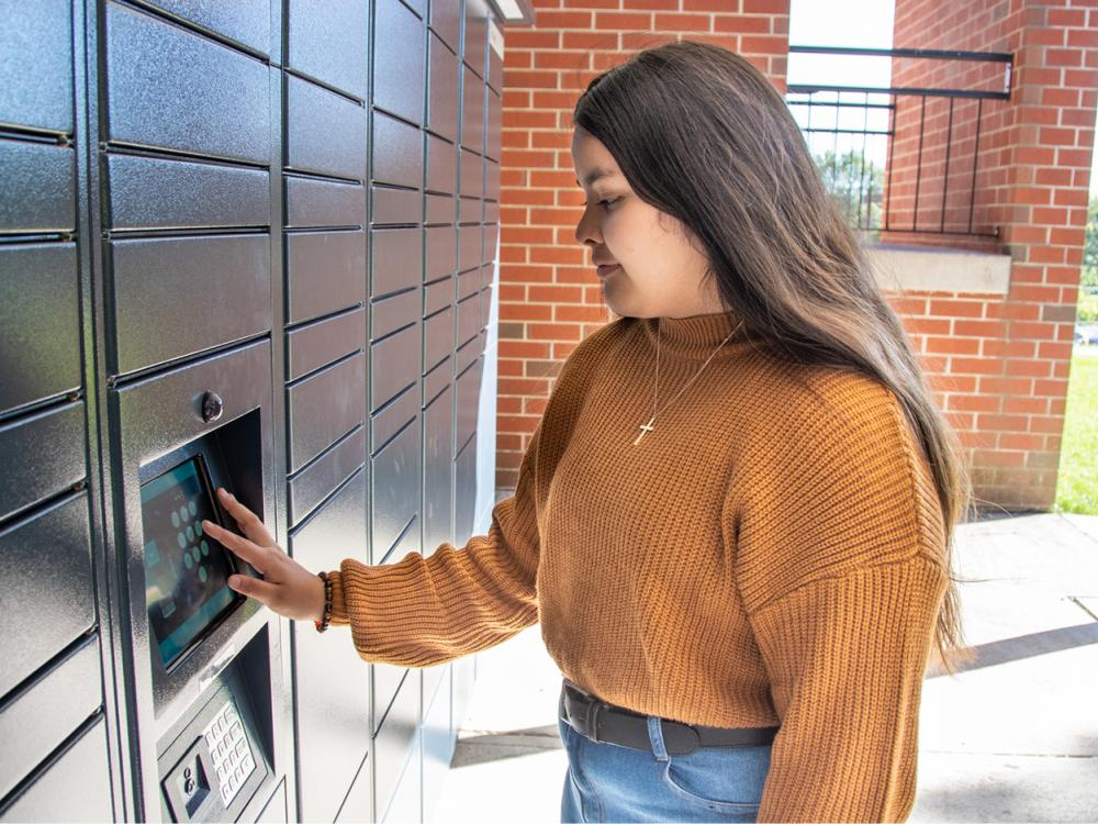 Student with long brown hair wears a burnt orange sweater and jeans as she types on a digital keyboard at navy lockers