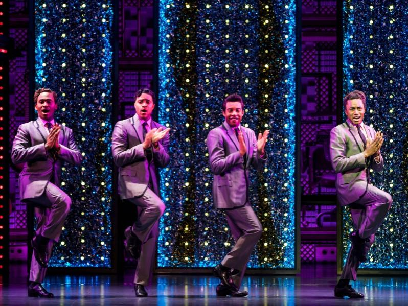 Four men wearing similar stage suits sing and dance in unison.