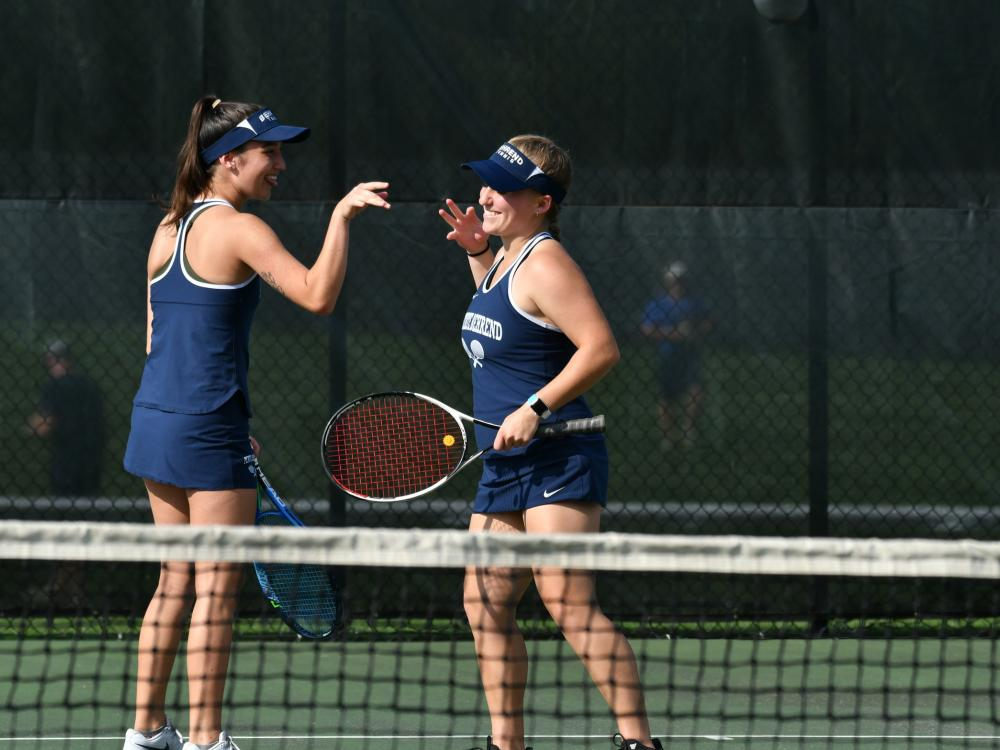Two Penn State Behrend tennis players congratulate each other after winning a point.