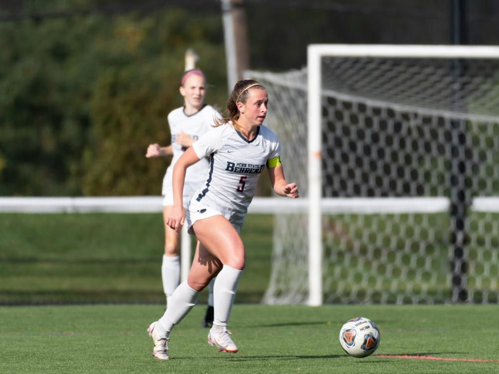 A Penn State Behrend soccer player prepares to kick the ball.
