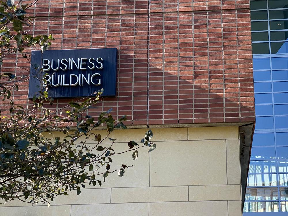 The sign for the Business Building is on a brick wall.