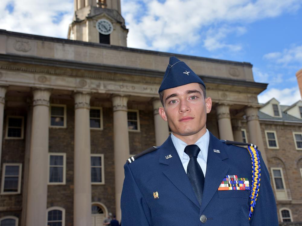 Cadet Josh Maldonado-Santiago stands in uniform in front of Old Main