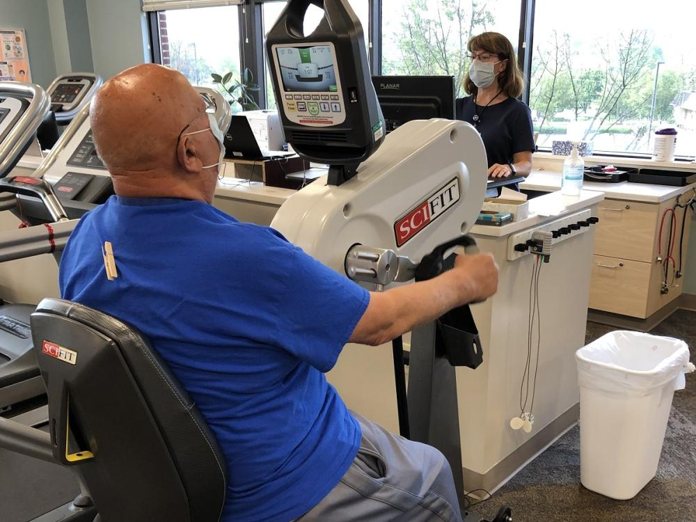 A man sits at an arm bike with his arms in the pedals. A woman exercise physiologist look at a monitor as she connects him to a heart monitor. Both are wearing face masks.
