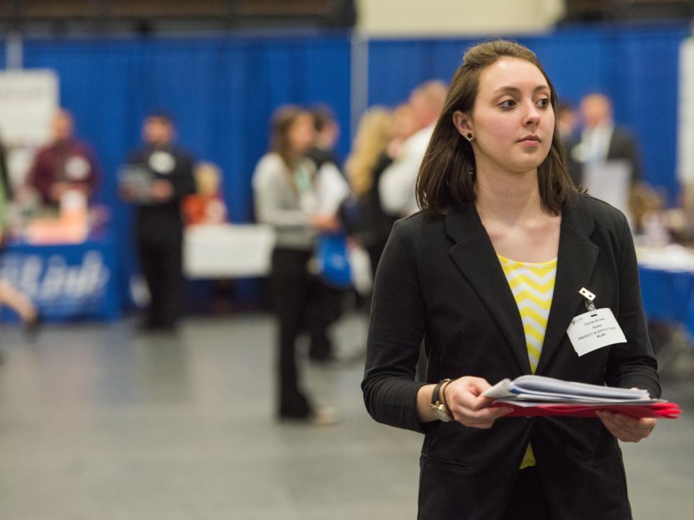 A female student walks down an aisle at a Penn State Behrend Career and Internship Fair