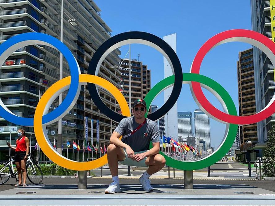 Gabe Castaño standing in front of the Olympic rings