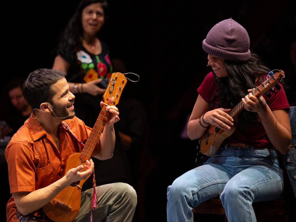 A man kneels next to a woman sitting in a chair while they both play stringed instruments.