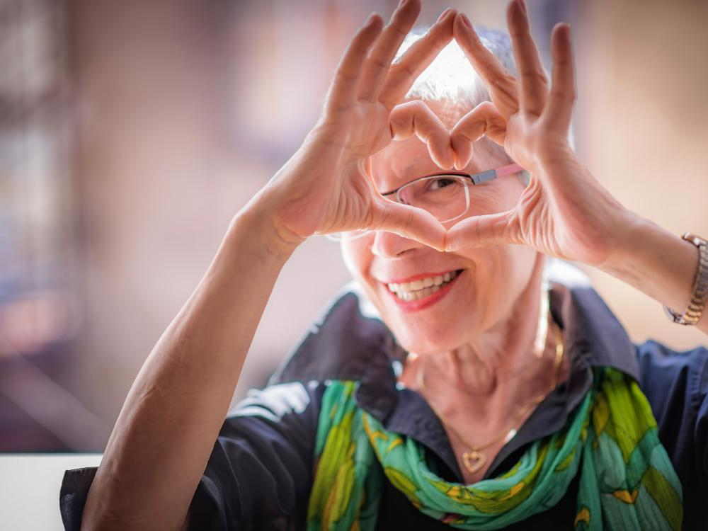Older woman making a heart shape with her hands