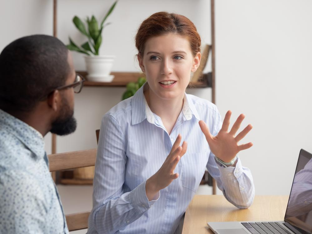 Man and woman talking near a laptop computer in an office setting.