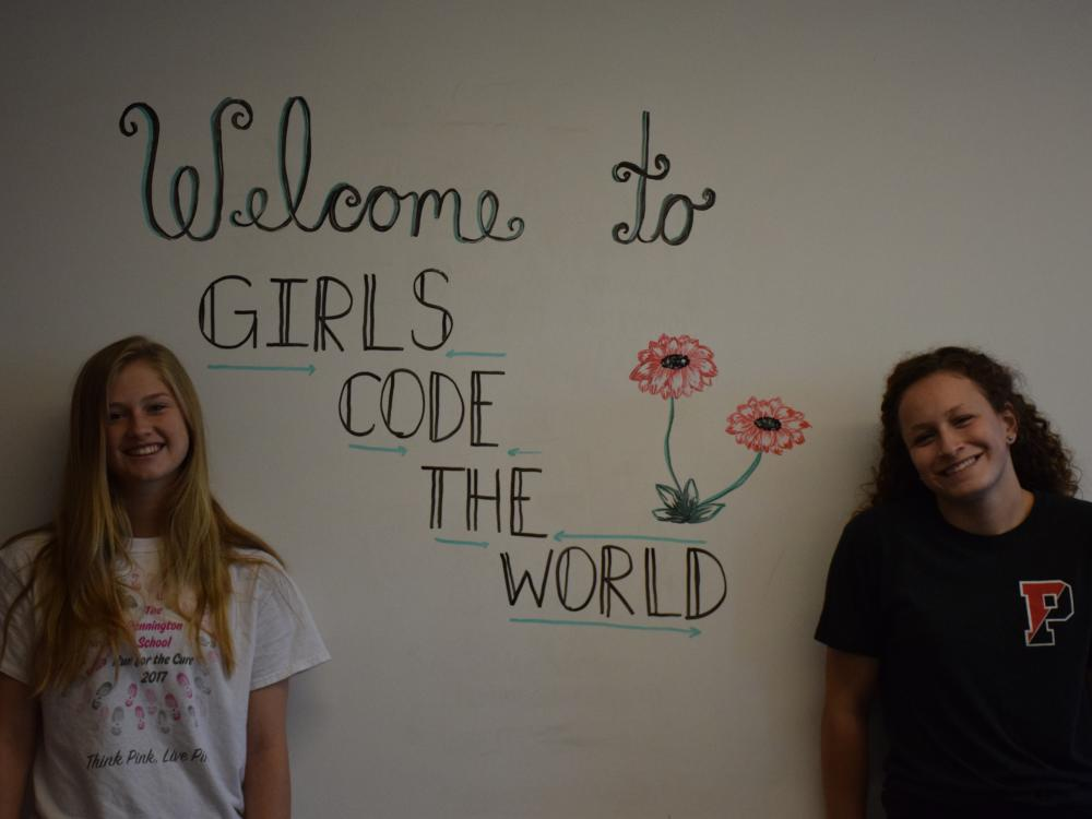"""Two young women stand in front of a wall saying """"Welcome to Girls Code the World."""""""