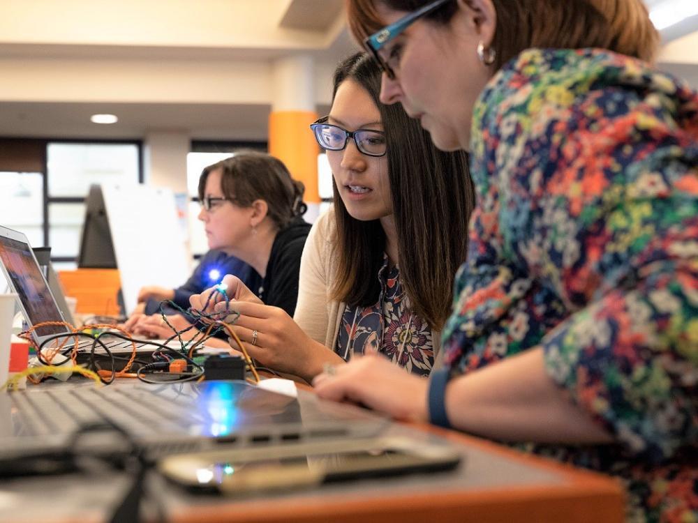Two women work with Hummingbird Duo robotics kit