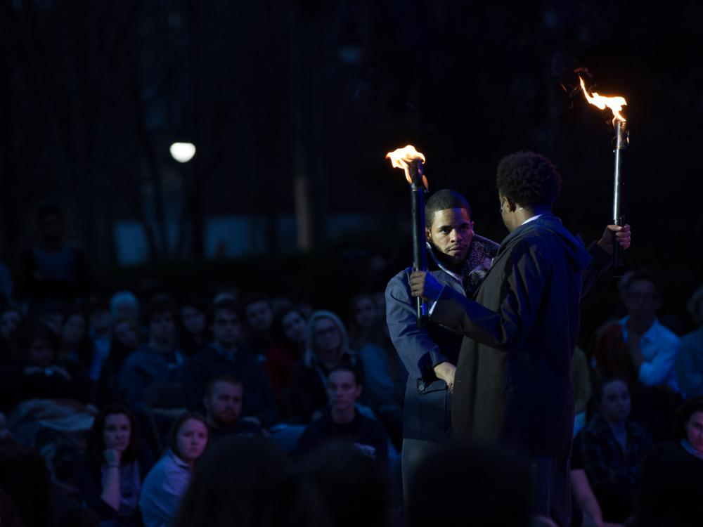 """Two """"Julius Caesar"""" actors interact with torches as the audience looks on."""