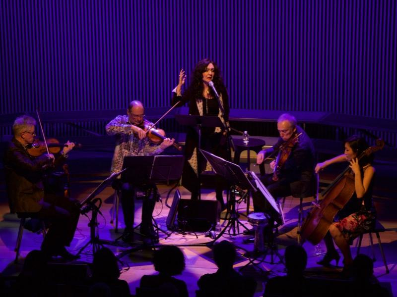 A woman stands in the center of a string quartet and sings.