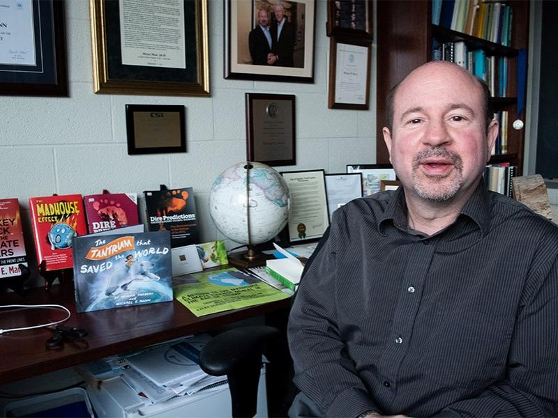 Michael Mann sitting in front of a table holding his many books on climate science.