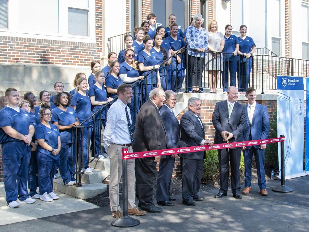Students wearing dark blue scrubs line stairs in front of a brick building. Six men wearing suits stand in front of them while holding a red ribbon to be cut by large gold scissors.