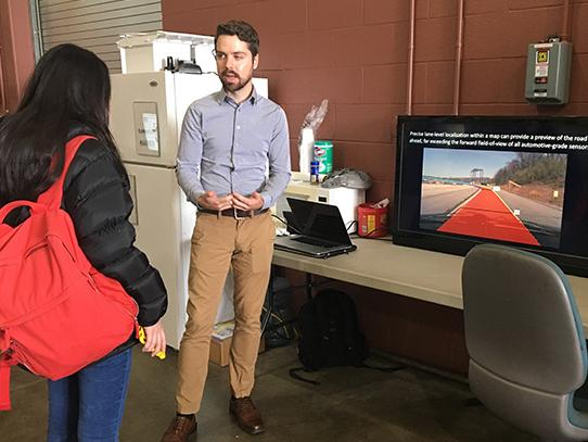 Man speaking with a woman in front of a TV screen.