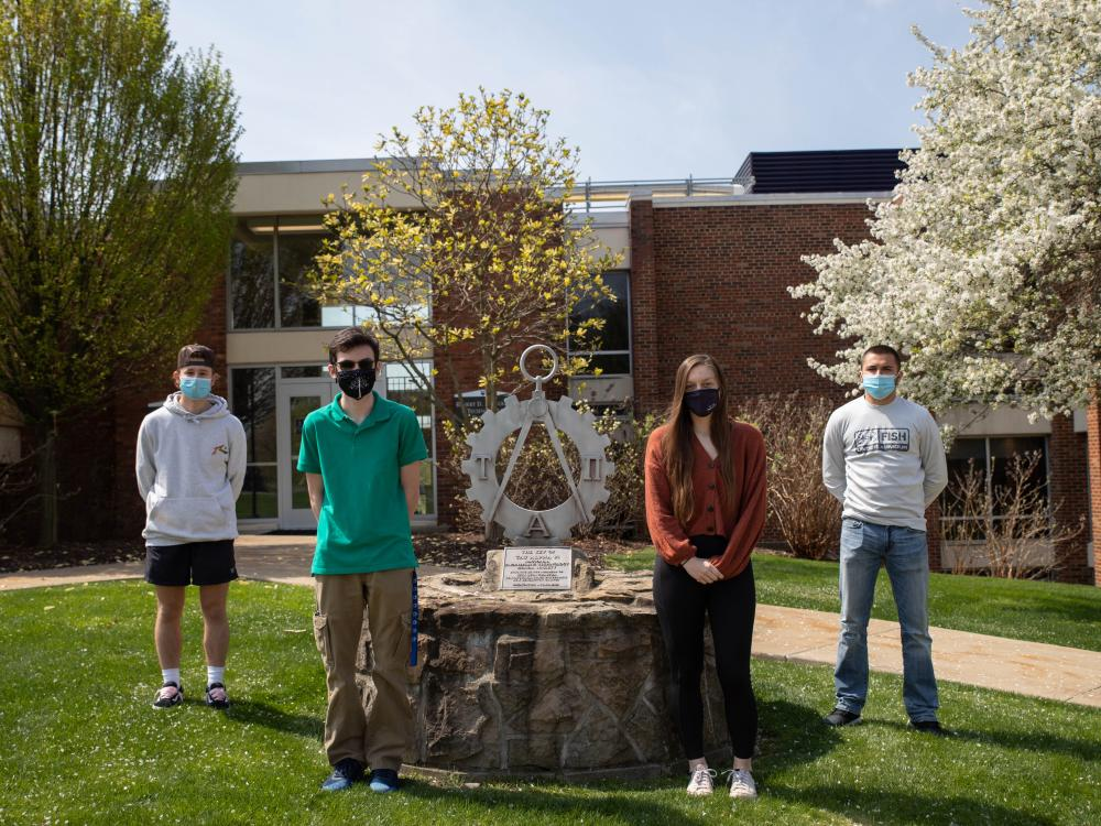 Four students stand outside by statue