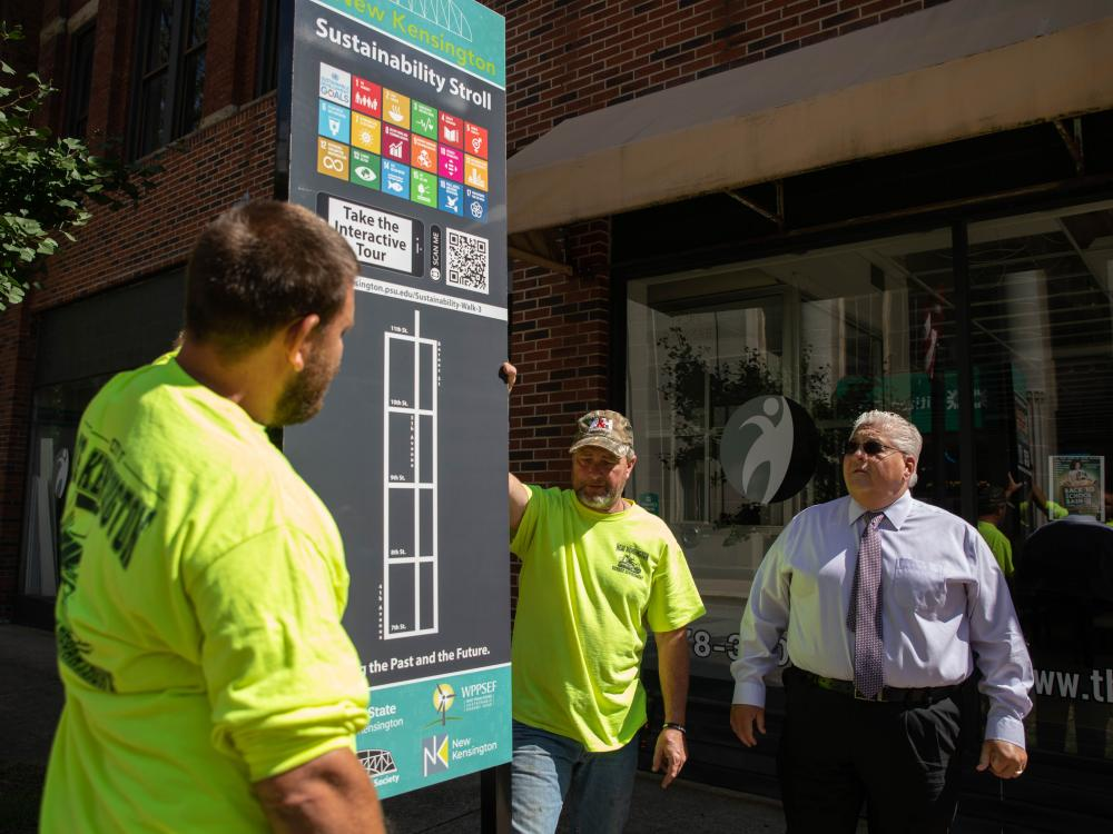 Three men look at street sign