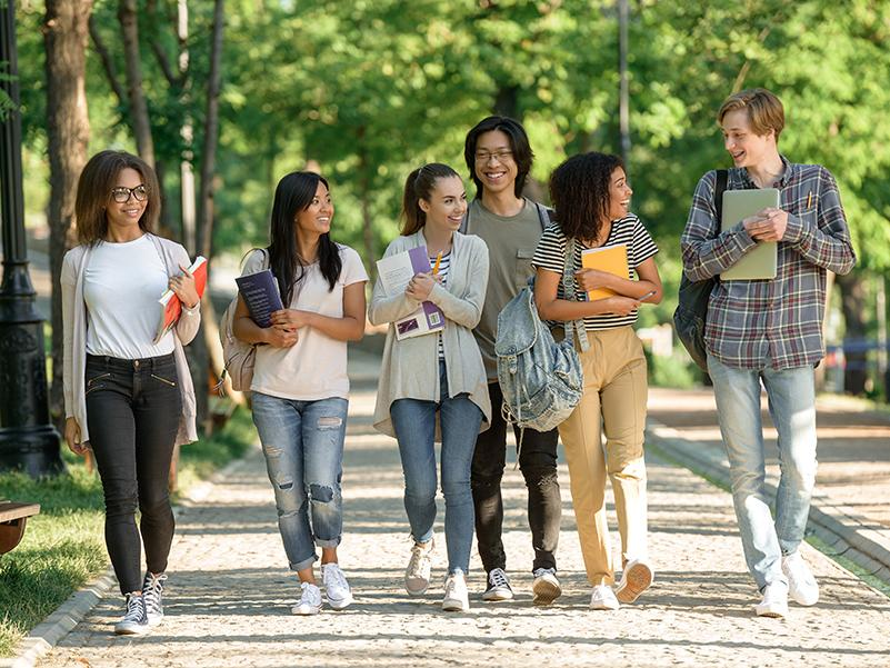 Six students walk outdoors on a college campus