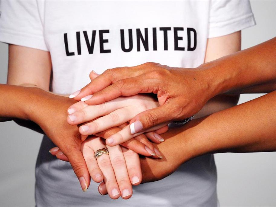 """Multiple pairs of hands stack on top of each other as a gesture of goodwill and teamwork, in front of a shirt that reads """"Live United"""""""