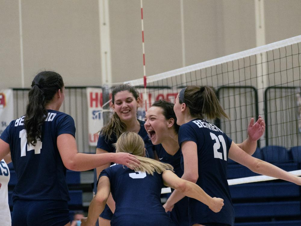 Members of the Penn State Behrend women's volleyball team celebrate a win.