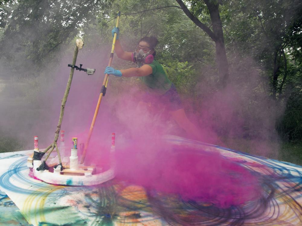 Artist paints in a cloud of pink smoke