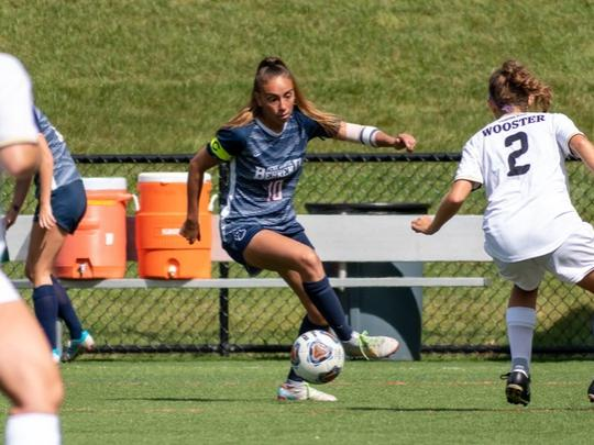 A Penn State Behrend soccer play dribbles the ball upfield.