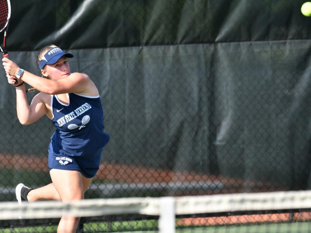 A Behrend tennis player hits the ball.