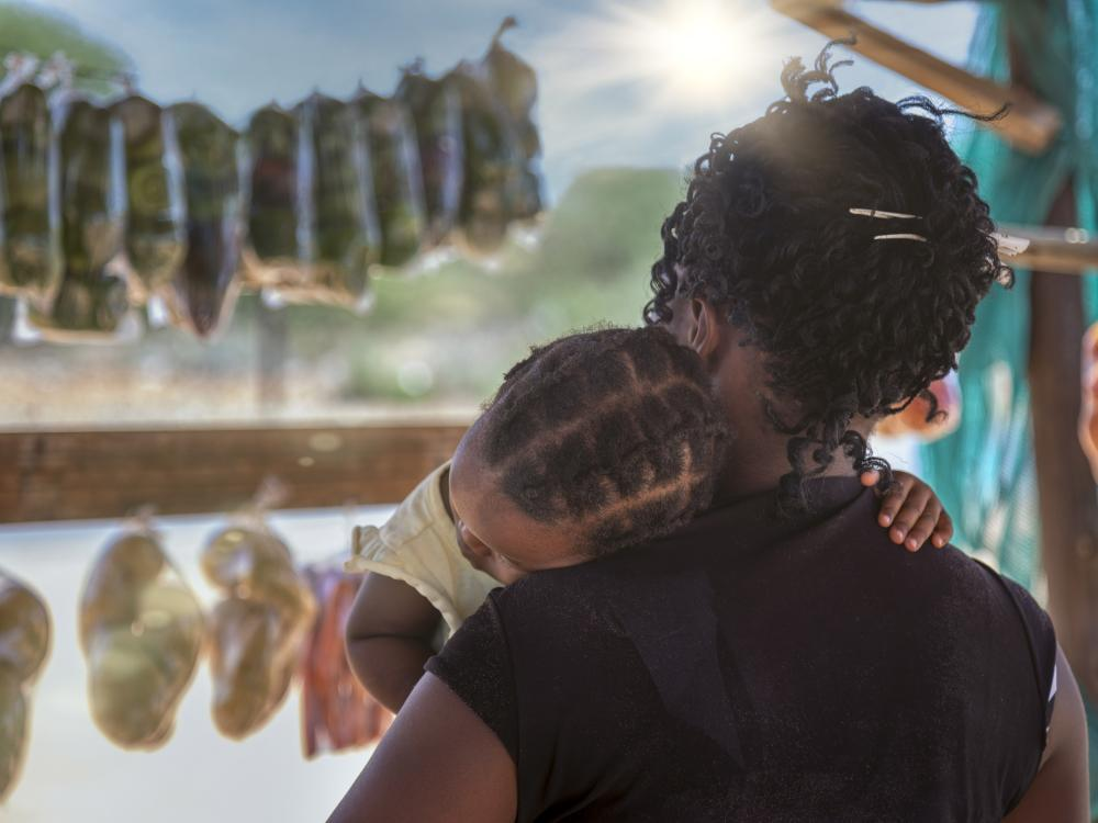 Woman seen from behind holding small child in her arms as she browses for food in an African market