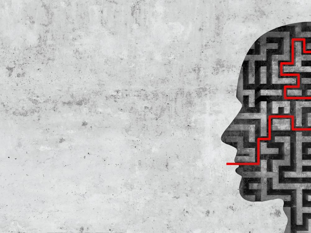 Graphic of the silhouette of a head with a maze overlaid