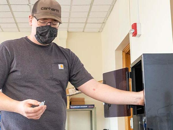 Dan Foust puts small plastic item into a 3D printer