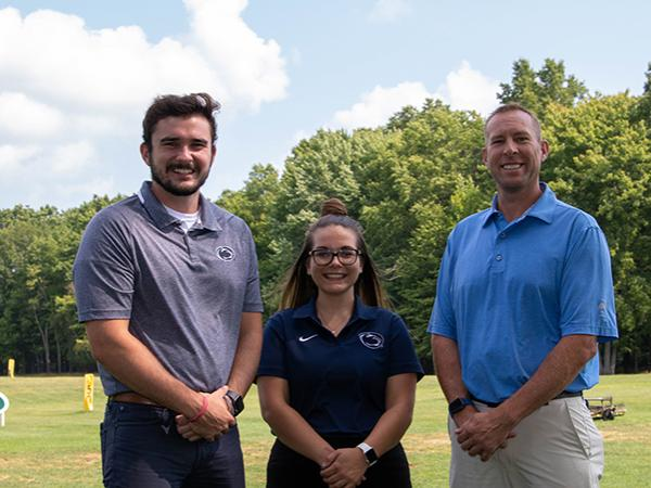Ty Cole, Amanda Howett, and Tom Roskos in front of golf driving range