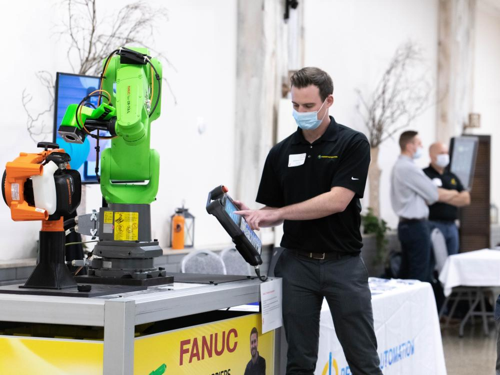 Man wearing mask holds digital tablet in front of robotic arm