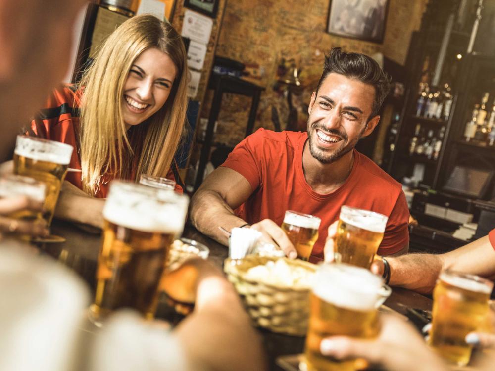 Young woman and man drinking at bar