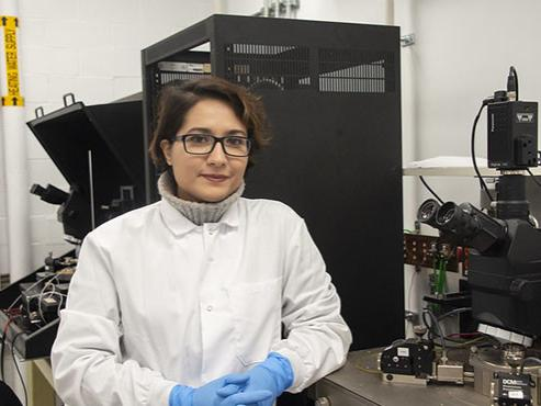 A professor in glasses stands in front of testing machinery in her lab.