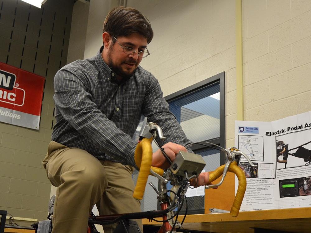 An engineering student demonstrates his project as part of the Student Showcase
