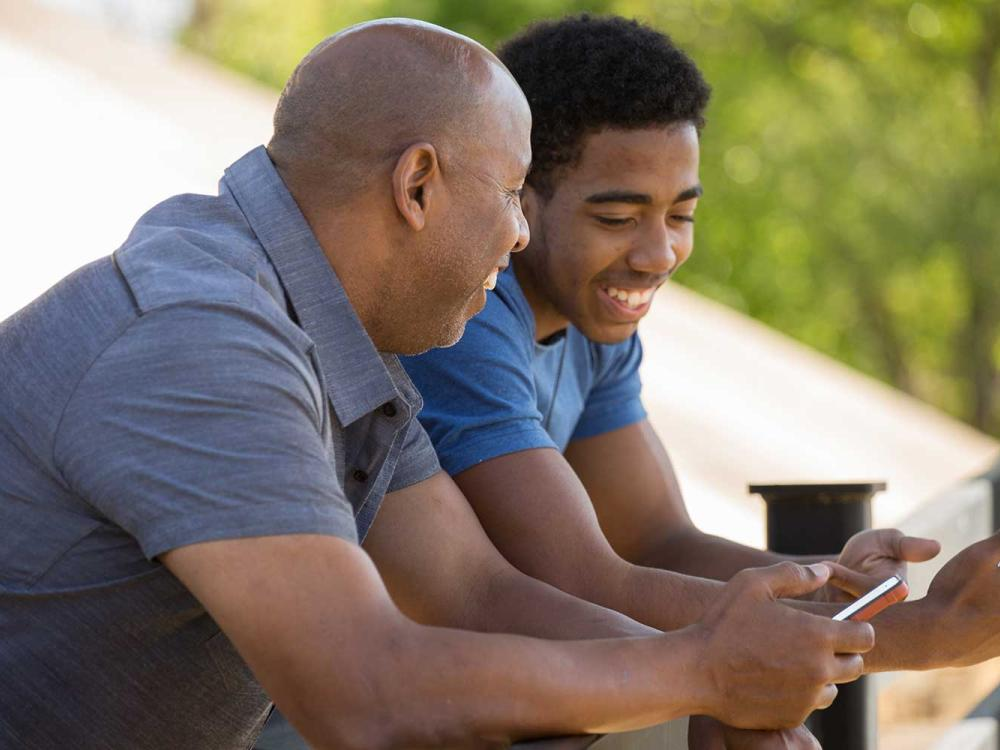 father and son talking and holding their mobile phones