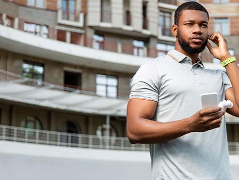 A man wearing a polo shirt and a fitness tracker on his wrist holds a smartphone while adjusting his headphones.