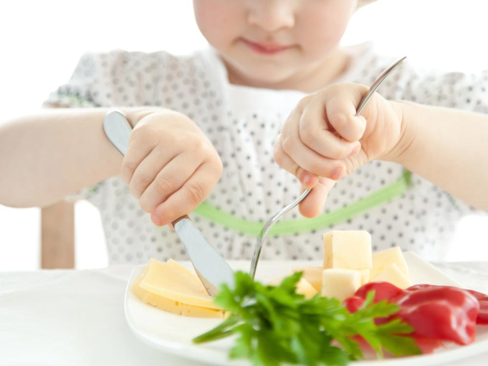 A young child using a knife and fork to eat a plate of vegetables