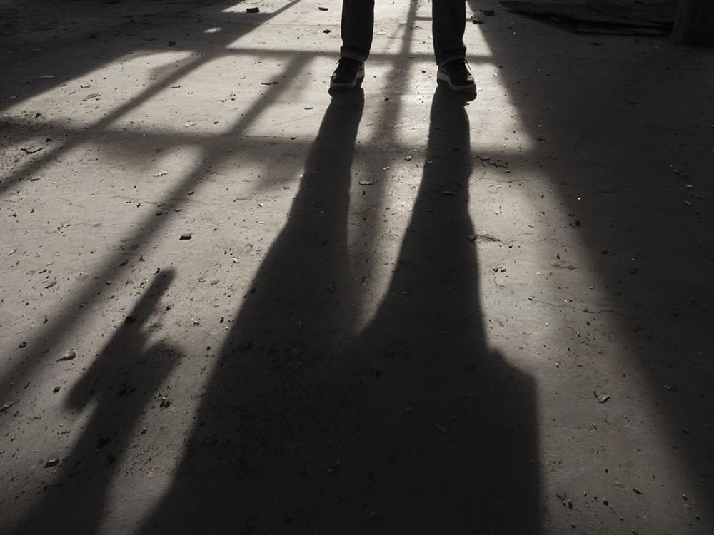 A person casts a shadow on the pavement. The photo focuses on the person's shoes, and their shadow reveals that they are holding a gun.