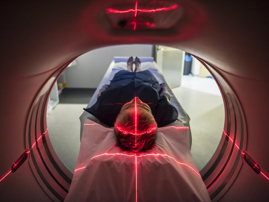 A woman enters an MRI machine with red laser lights covering her head and torso.
