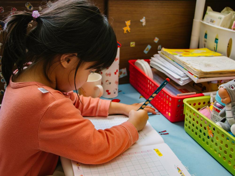 Young girl with black pony tail and orange shirt completing worksheet