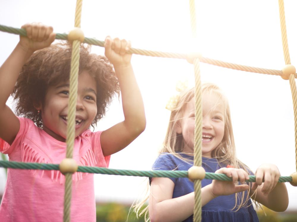 Two small children smiling and climbing on a rope course