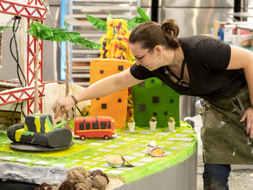 A woman uses a sculpting tool to manipulate fondant on a tank-shaped cake as part of a larger edible landscape.