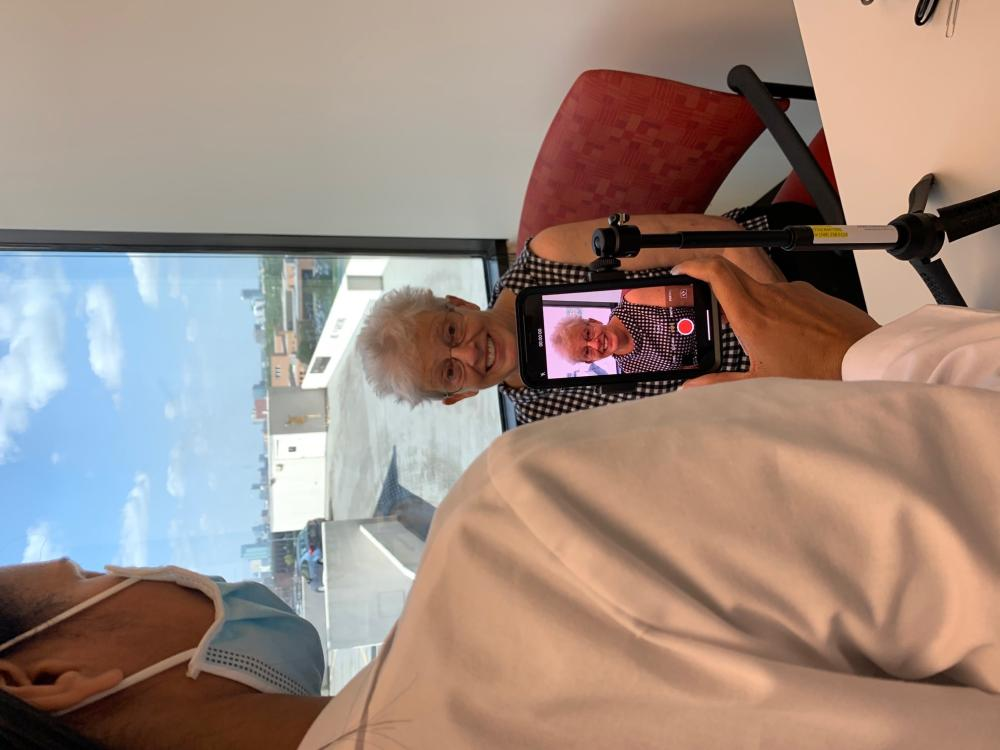 An elderly patient participates in a video test on a smartphone held by a female nurse practitioner