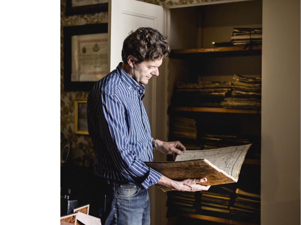 Man holding an old ledger listing grape production in front of a closet containing 200 years worth of ledgers